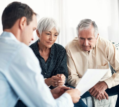 Shot of an older couple being given advice by a sales representative, in the home